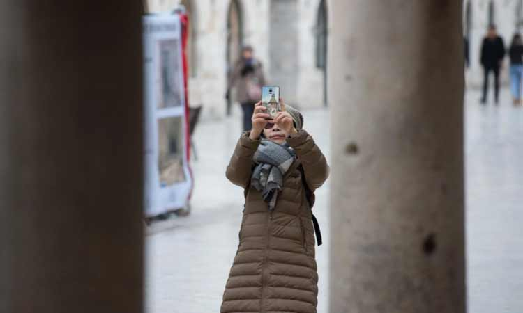 asain tourist in dubrovnik snow