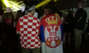 Two young ladies share the love by wearing Croatian and Serbian flags
